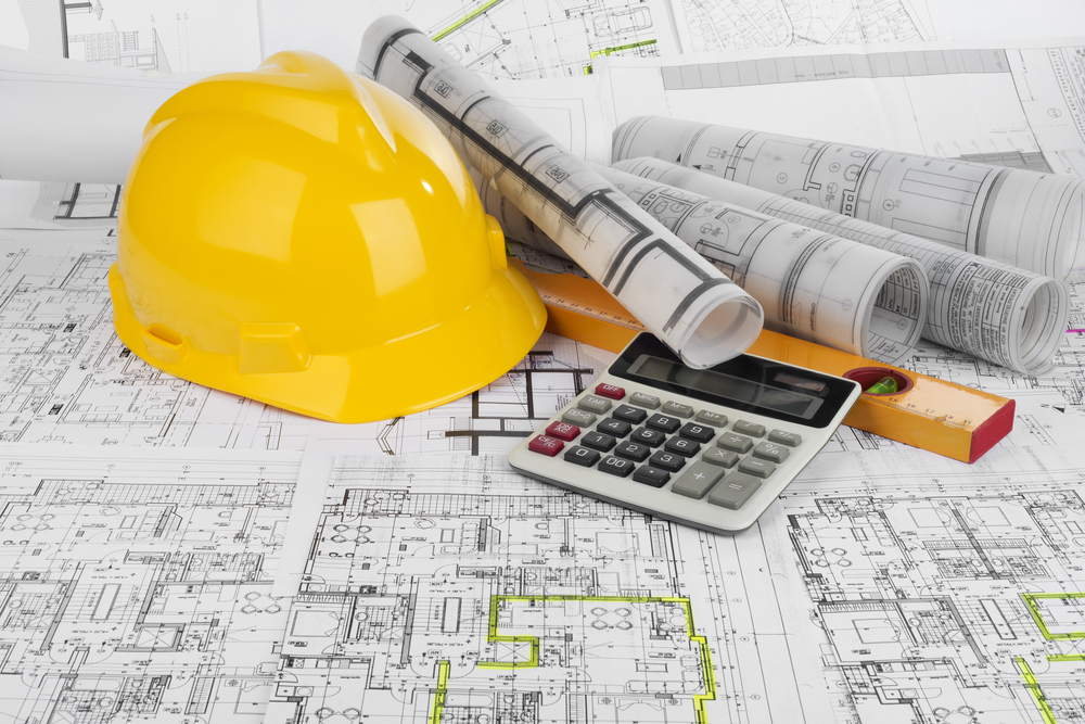Image of yellow safety hat, blueprints, calculator and design tools
