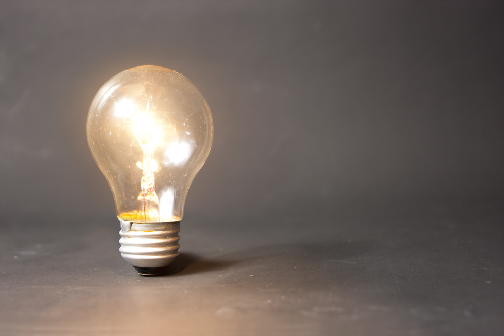 Image of lit lightbulb on gradient grey background