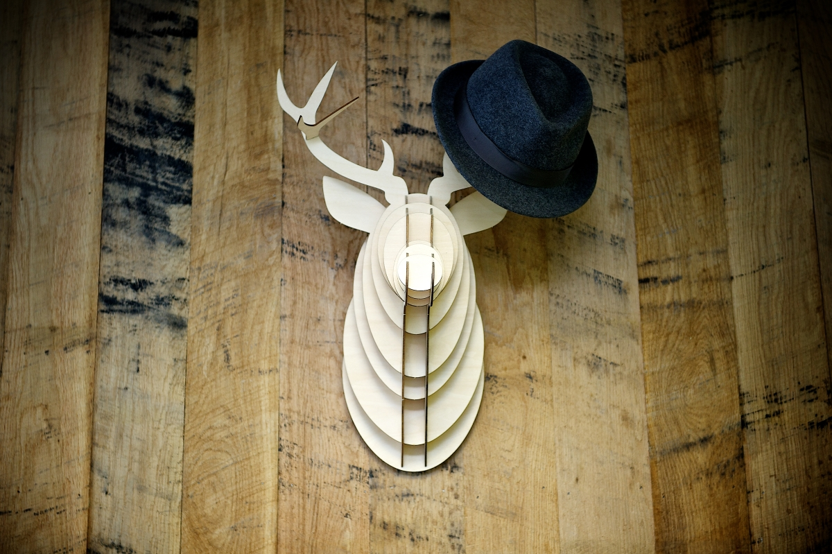Image of modern art deer head in wood with hat hanging from antlers