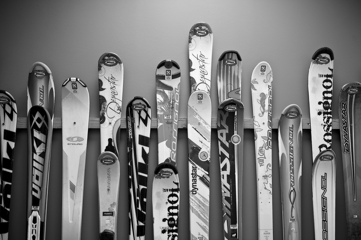 Black and white image of skis resting again wooden frame