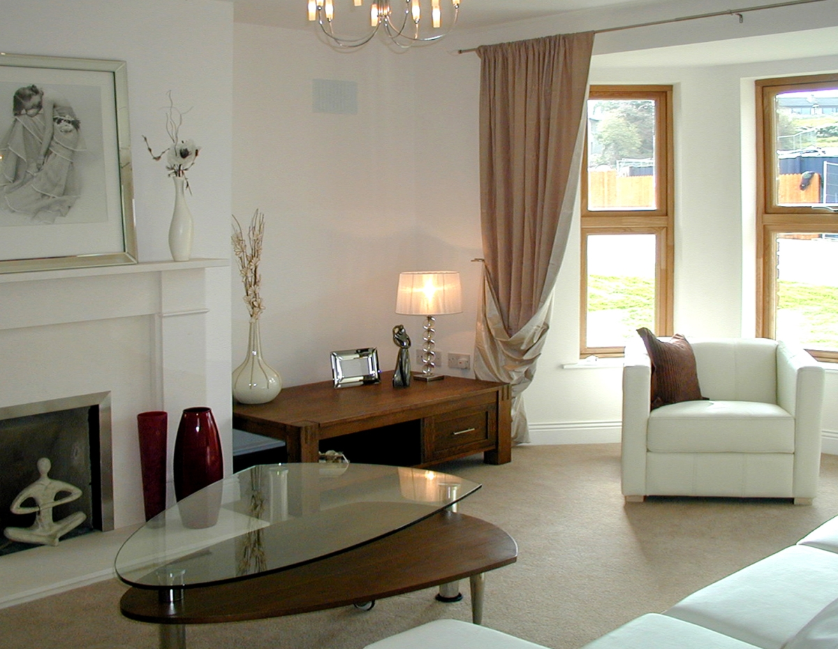 Image of living room with white, wooden tables and red accents