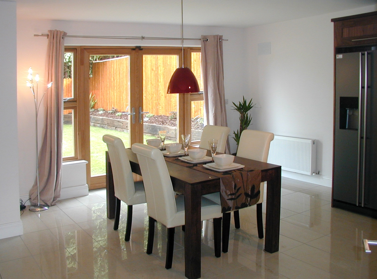 Image of wooden dining table, white chairs and red accent lighting