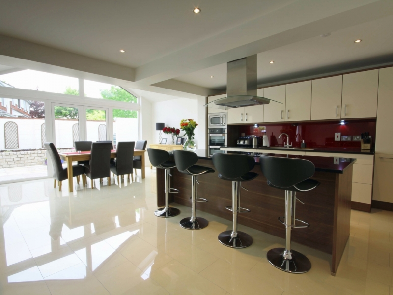 Interior image of dining table, kitchen with bar stools and island