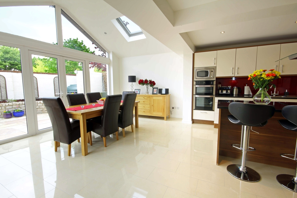 Image of dining table looking out patio doors to cultivated garden space
