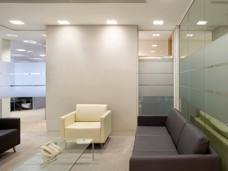 Interior image of office reception space with chocolate and cream furniture and glass walls