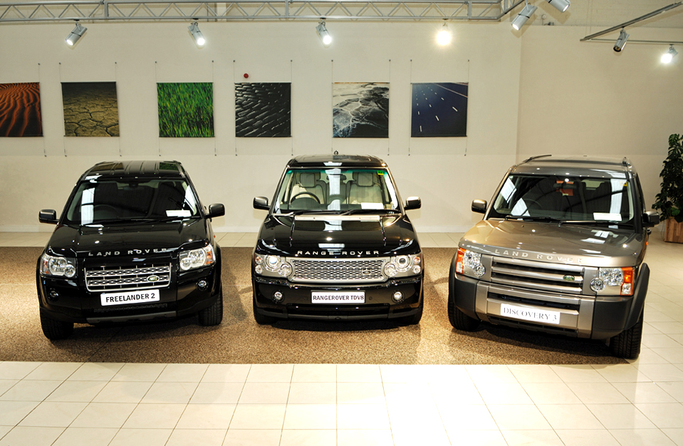 Image of showroom floor with three range rovers and art hanging on back wall
