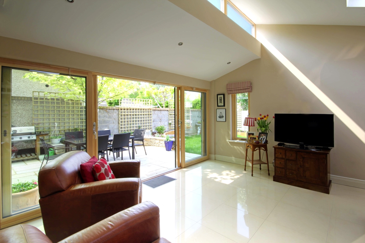 Interior view of new extension looking into the garden with light streaming in from skylights