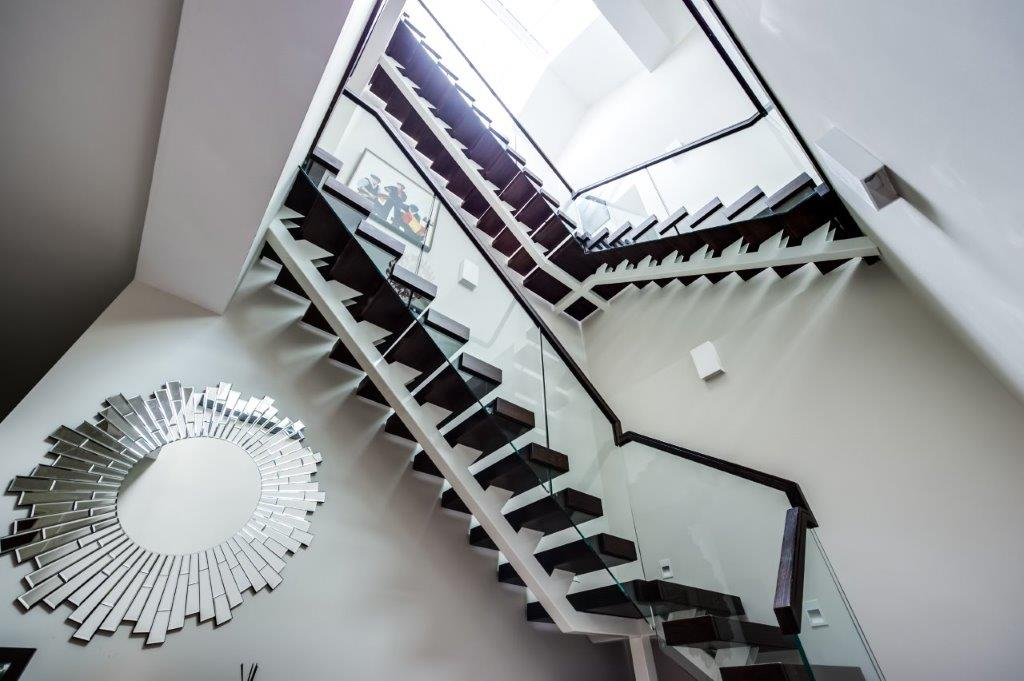 Looking up the open tread staircase in detached house